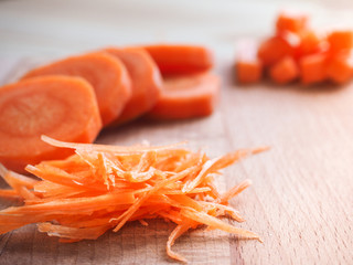Coarsely chopped carrots on a wooden table.