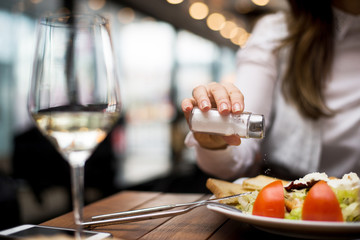 Woman adding salt to food in restaurant. Wall mural