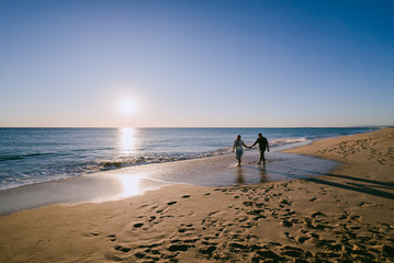 Couple on a beach at sunset in Portugal