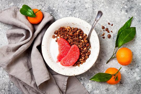 Healthy winter breakfast. Greek yogurt bowl with chocolate gingerbread granola and grapefruit. Top view, flat lay, overhead