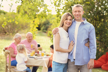 Happy couple with family having barbecue party outdoors