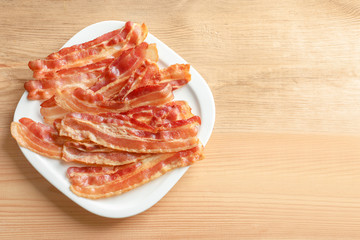 Plate with cooked bacon rashers on wooden table