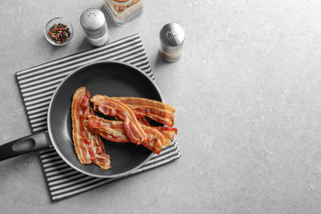Pan with cooked bacon rashers on table