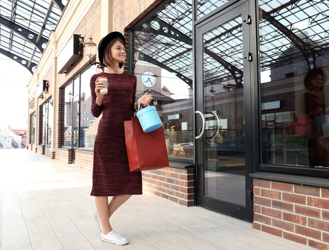 Beautiful woman with shopping bags and cup of coffee at strip mall