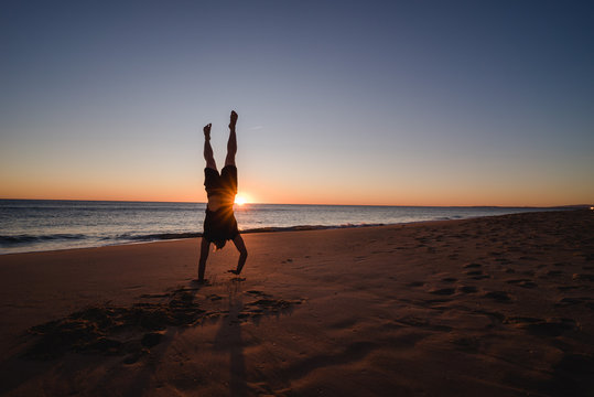 Man doing handstands on the beach at sunset in Portugal