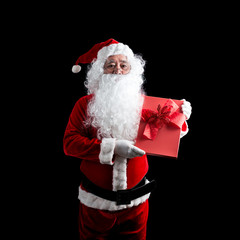 Photo of happy Santa Claus with red gift box of Christmas present in hands, isolated on black background.
