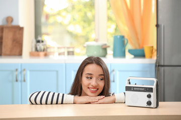 Young woman listening to radio in kitchen