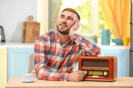 Young man listening to radio in kitchen