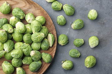 Wooden plate with fresh raw Brussels sprouts on table