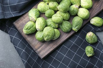 Wooden board with fresh raw Brussels sprouts on table