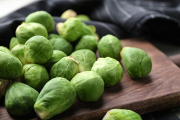 Wooden board with fresh raw Brussels sprouts on table, closeup