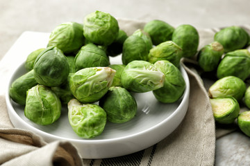 Plate with fresh raw Brussels sprouts on table