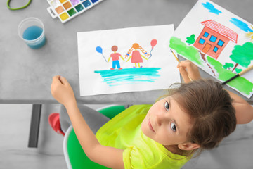 Little girl painting at table