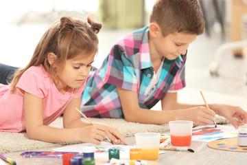 Little children painting on floor