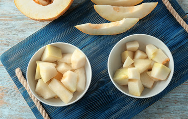 Bowls with yummy melon slices on wooden table