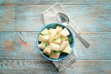 Bowl with yummy melon slices on wooden table