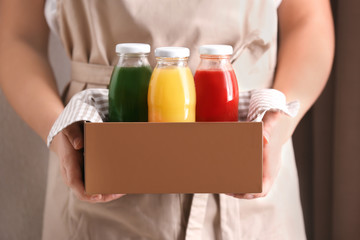 Woman holding wooden crate with delicious juices in bottles