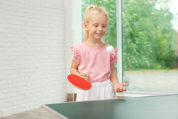 Cute little girl playing table tennis indoors