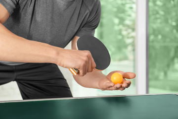 Man playing table tennis indoors
