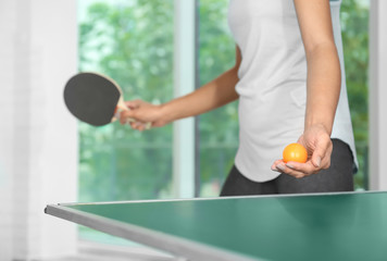 Woman playing table tennis indoors