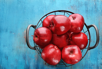 Basket with delicious red apples on table