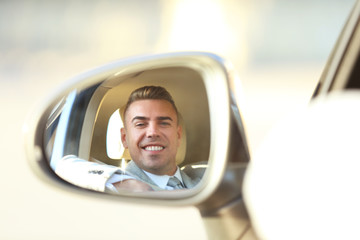 Reflection of adult man in rear view mirror of car