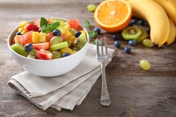 Bowl with delicious fruit salad on table