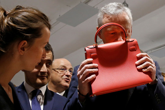 """French Minister Finance Bruno Le Maire smells a leather luxury bag as he visits the new logistic hub of """"Vestiaire Collective"""" an online marketplace to buy and sell pre-owned designer clothing and accessories, in Tourcoing"""