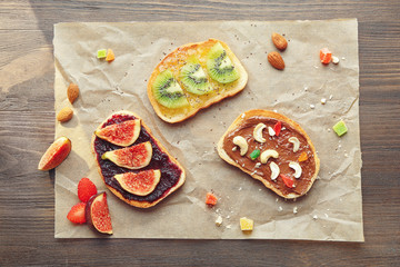 Delicious toasts with jam and chocolate paste on parchment