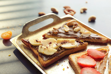Delicious toasts with chocolate paste, fruits and nuts on metal tray