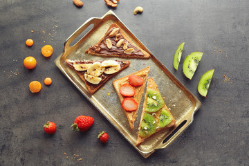 Delicious toasts with chocolate paste, peanut butter and fruits on metal tray