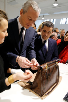 """French Finance Minister Bruno Le Maire and Minister for Public Action and Accounts Gerald Darmanin, check a leather luxury bag as they visit the new logistic hub of """"Vestiaire Collective"""" an online marketplace in Tourcoing"""