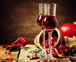 Pomegranate liqueur, rustic style, vintage wooden background, selective focus