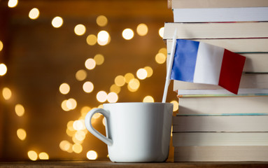 White cup with France flag near books