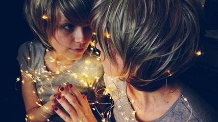 Mujer joven rodeada de luces de navidad reflejándose en un espejo