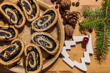Sliced Bejgli (Poppy seed roll) and christmas ornaments, on wooden background.