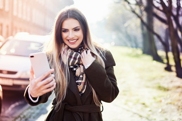 Young woman taking selfie while on walk on sunny winter day in the city