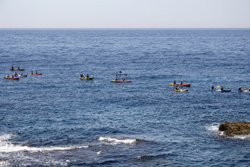 Many people ride water kayaks in front of Dubrovnik old town in blue Mediterranean sea in summer.