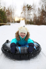Little girl on snow tubes downhill at winter day
