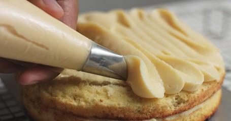 Adding cream and fruit to cake