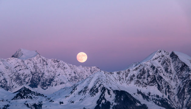 full moon rising in winter in the Swiss Alps over mountains near Klosters in the Raetikon mountain range