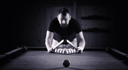 A man with a beard plays a big billiard. Party in a 12-foot pool
