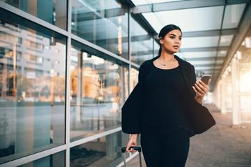 Businesswoman walking outside public transportation station