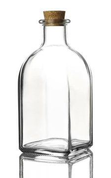 Empty transparent glass bottle of a square shape with a cork stopper on a reflective surface, isolated on a white background.