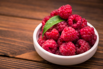 Red fresh raspberry in bowl