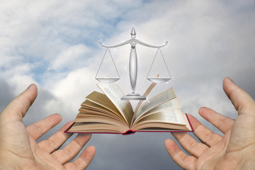Hands of the lawyer show the scales and the book of justice.
