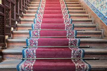 Front view of old ascending wooden stairs with ornate red carpet and wooden balustrade
