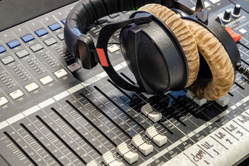 Headphones are placed on the audio controller in recording room.