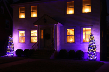 Christmas and New Year holiday background. Private house exterior view with decorated for Christmas and New Year holidays season outdoor trees glowing in the dark. Night scene.