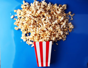 Paper cup in red and white with popcorn on color background